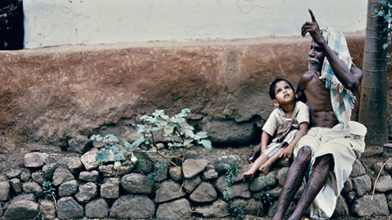 An elderly village man pointing up and a young boy sit close together on a stone wall next to a masonry building.