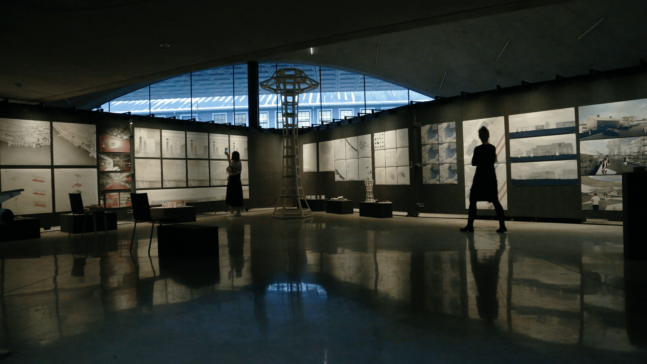 A person standing in a dimly lit room with a ceiling cutout.