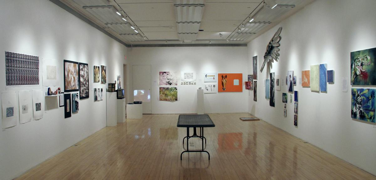 view of a gallery with white walls and many pieces hung on the walls