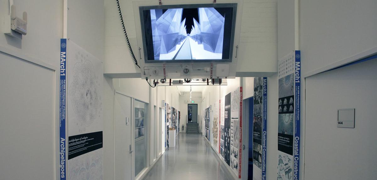 view of a white hallway with posters hung on both sides and a monitor hanging from the ceiling