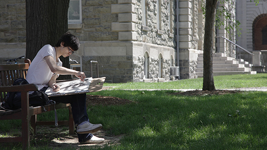 student sketching on a bench outside a brick building in the summer