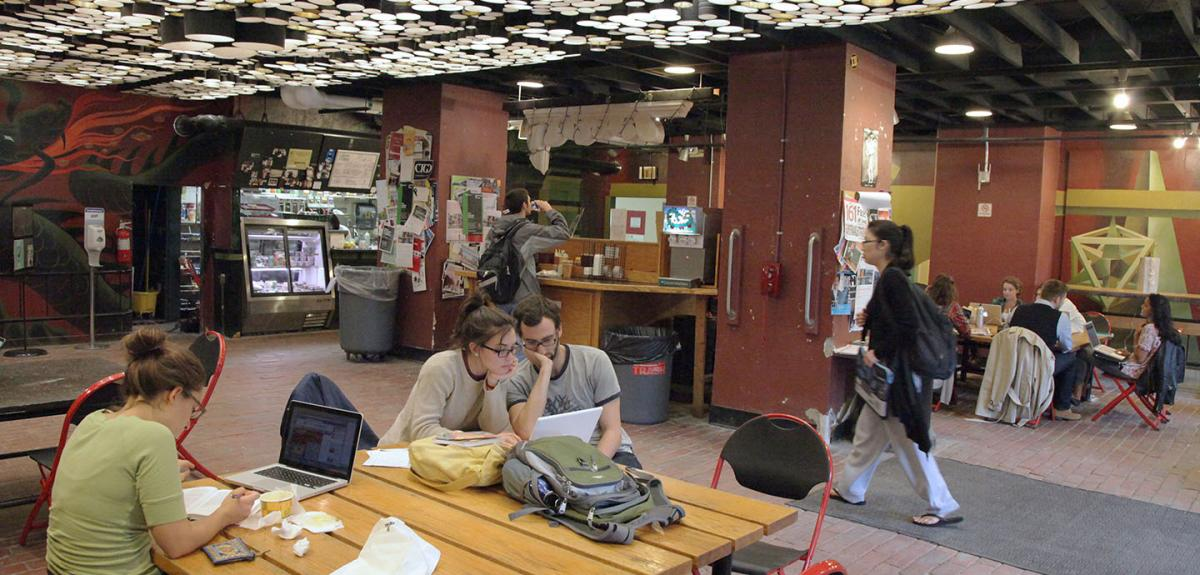 Activity happening in the Green Dragon Cafe including people at tables eating and working on computers.