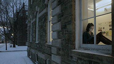 Student sitting on window sill of West Sibley Hall