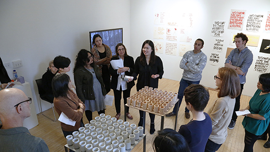 students and faculty engaged in conversation in front of a sculpture of dozens of cups