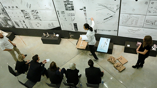 overhead image of students presenting architectural work and models during a review