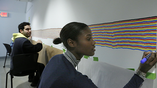 students drawing a series of colored parallel lines on a white wall