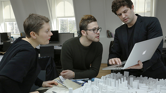 student and faculty discuss an architectural model
