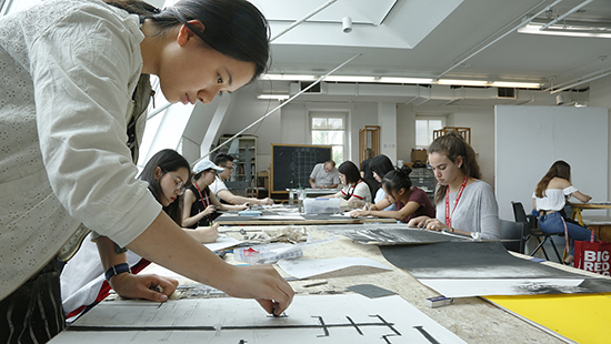 students drawing and painting in a large studio with skylights