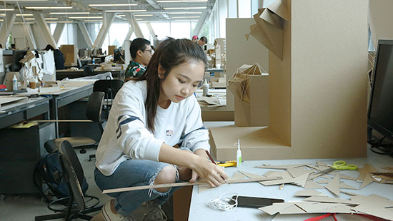 student in foreground working on cardboard project in the L. P. Kwee Studio
