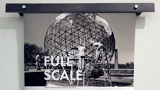 The top portion of a black and white poster depicting a metal globe being constructed by three men on ladders