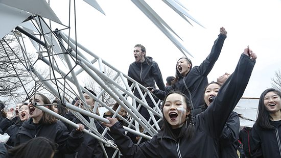 students wearing black raincoats and white and black makeup celebrate on a large white metallic structure.