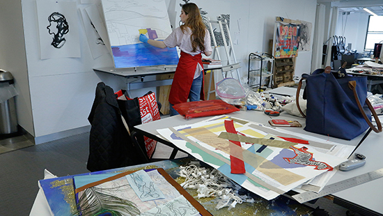 student painting in a cluttered studio