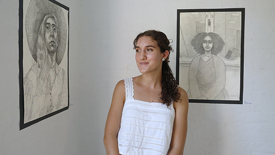 young woman in front of two black and white sketches hung on a gallery wall