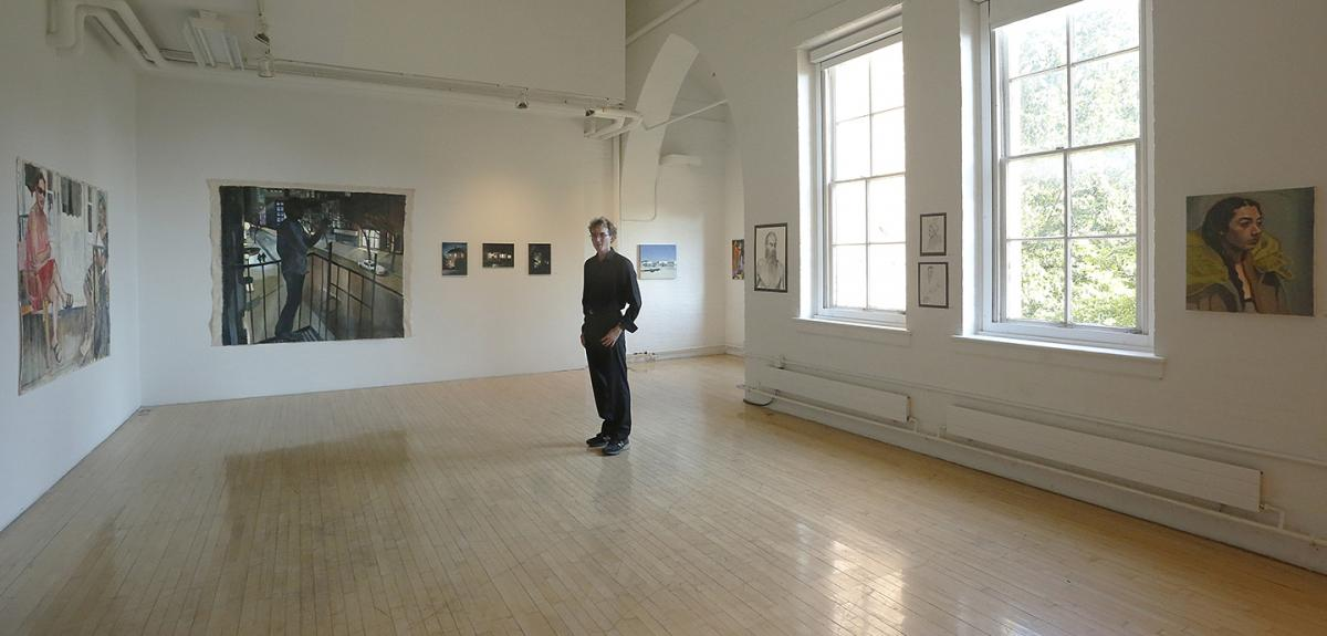 young man dressed in black standing in a gallery with large windows and wooden floors