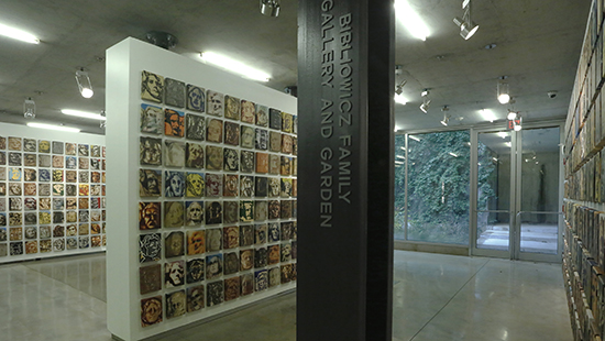 gallery view of several walls hung with hundreds of square-sized portraits of faces