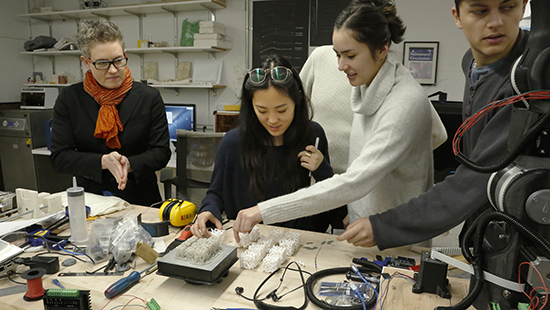 students and faculty work with a computer on a series of small cubed objects on a desk with wires
