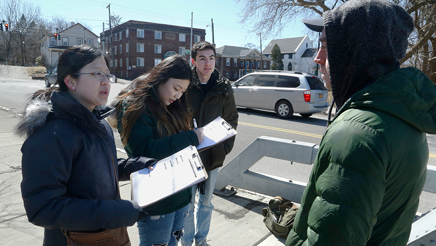 students with clipboards talk to a man in a small town on a sunny day
