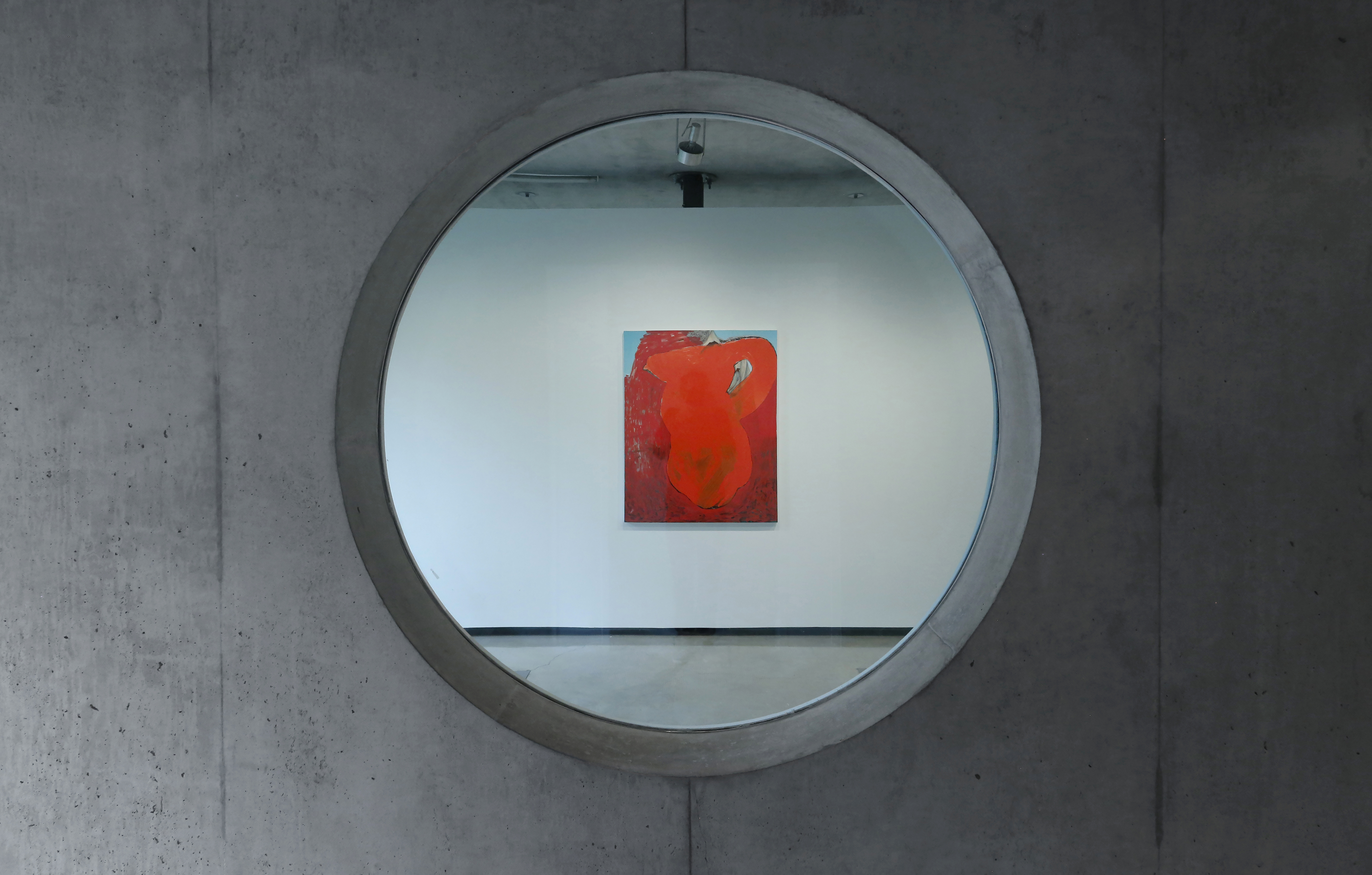 A concrete wall with a cuout and  red painting on an adjacent concrete wall.