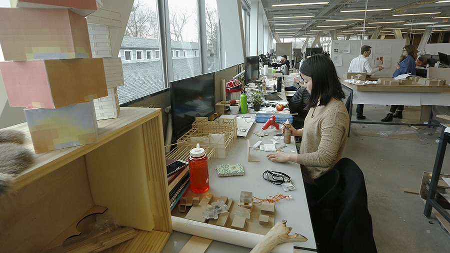 students work in a modern architecture studio with windows in front looking onto an older grey building