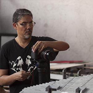 Image of a man wearing glasses and a dark t-shirt taking a picture of sculpture work.