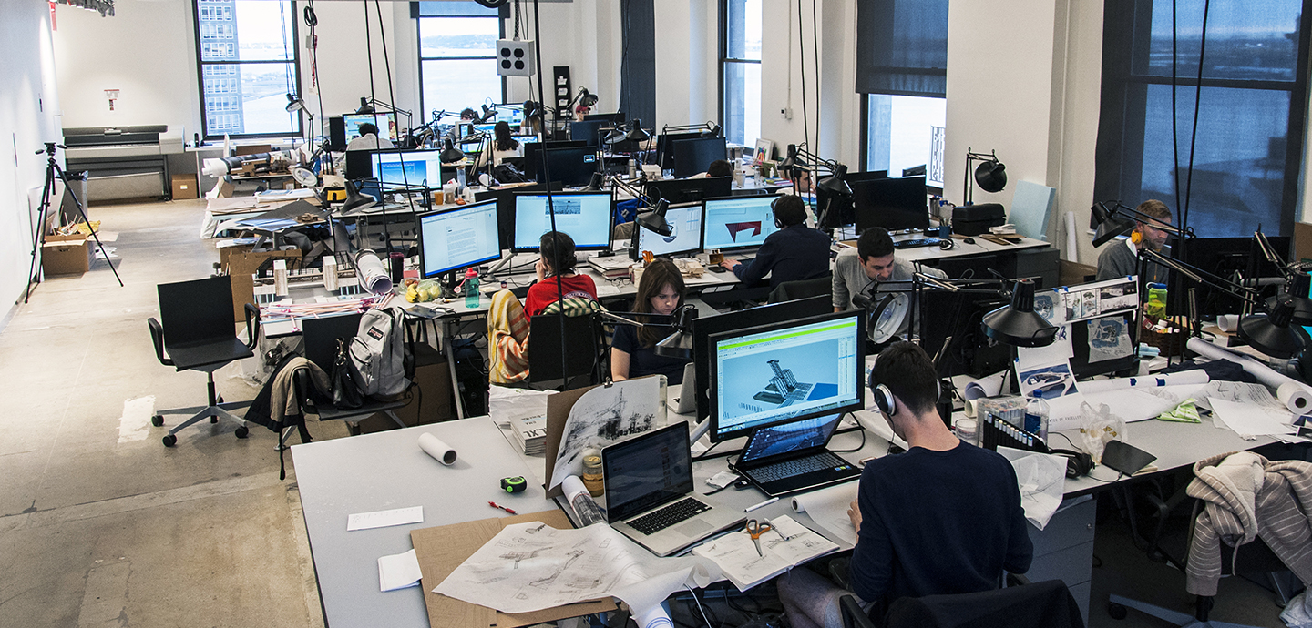studio with students working at computers and a view of New York City harbor