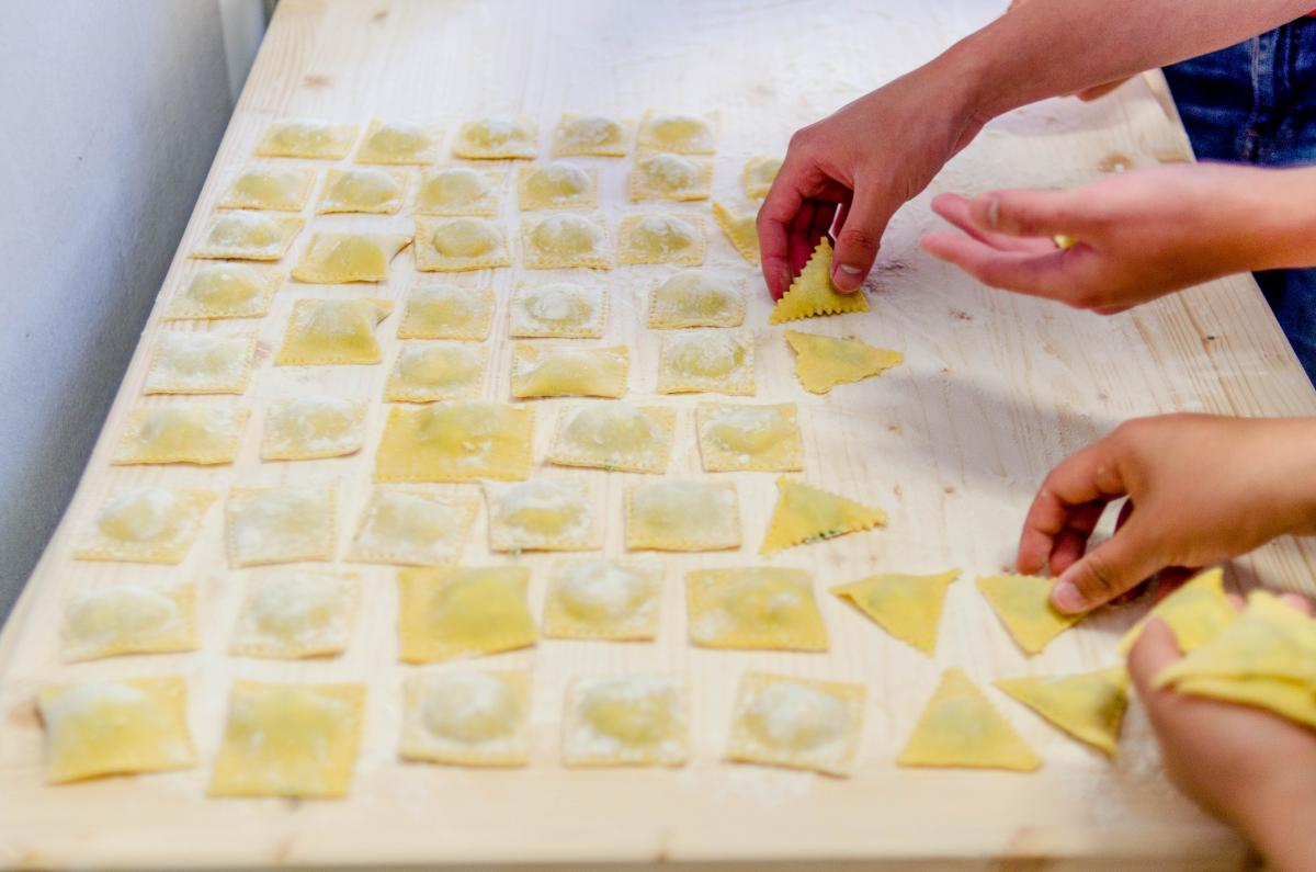 hands shaping square pasta on a wooden table