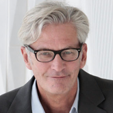 headshot of a man with black glasses and white hair