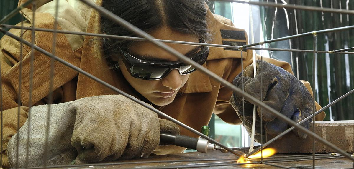 close up of a woman using a welding tool while wearing protective glasses and gloves