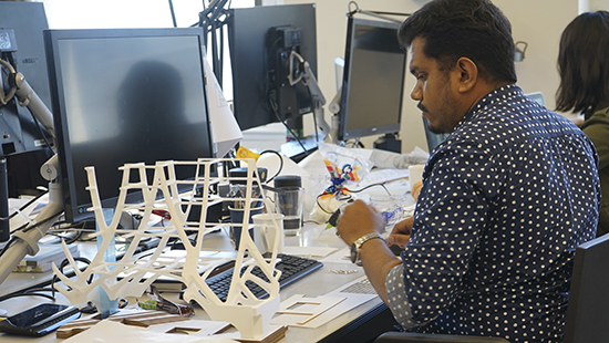 and working with a white scaffolding model in an architecture studio
