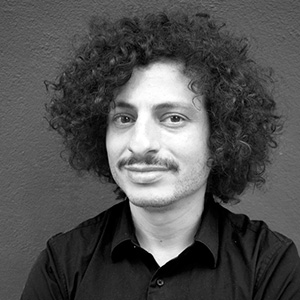 A person with thick curly dark hair and mustache, a dark top