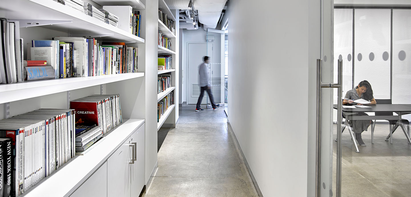 books on shelves on left with view on right of student in classroom