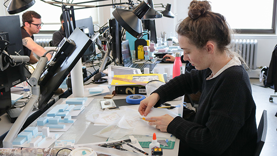 a woman works on a model on a messy desk in a studio with other desks and computers behind her