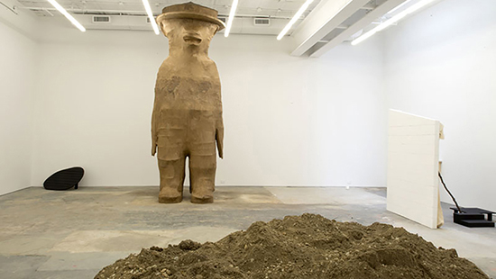 large wooden sculpture of a bear in a white room