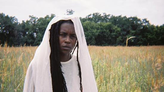 Photo of a woman in a field of grass wearing a white headscarf