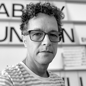 A person with large spectacles, curly hair, and a striped shirt.