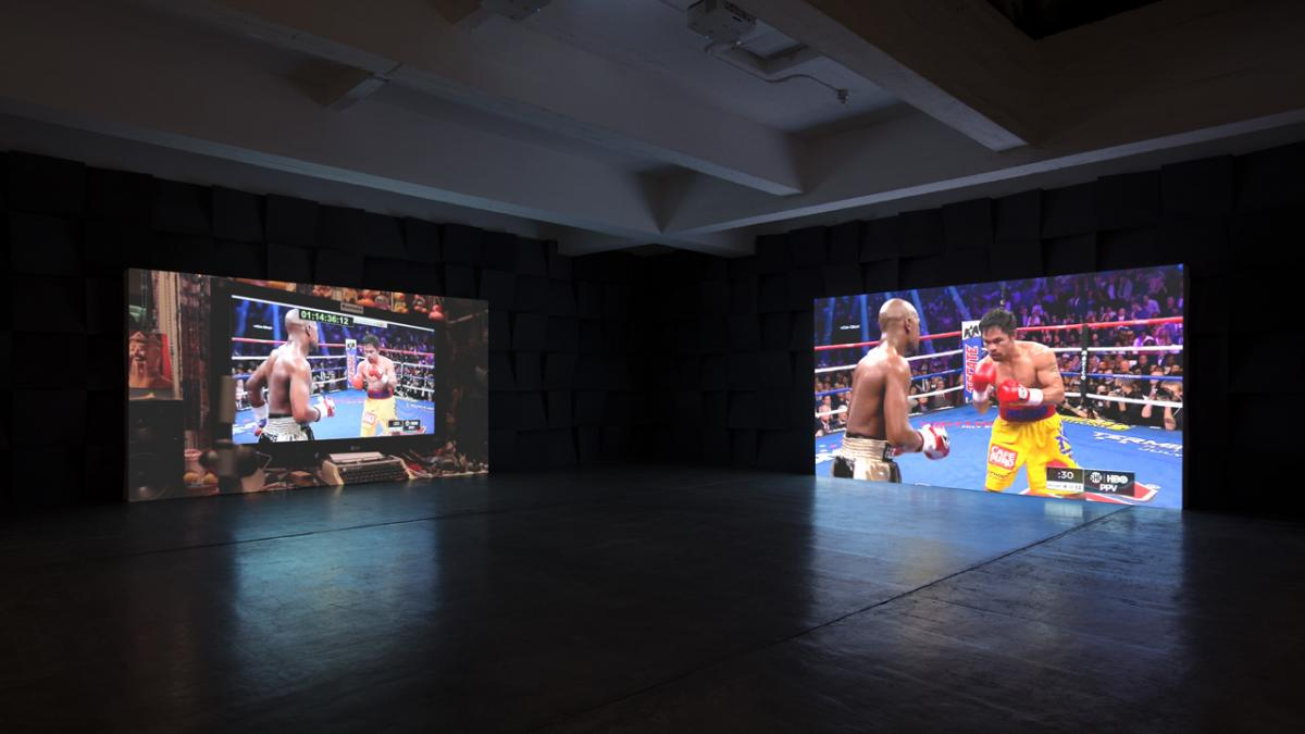 dark room with two large screens with different projections of a boxing match on them