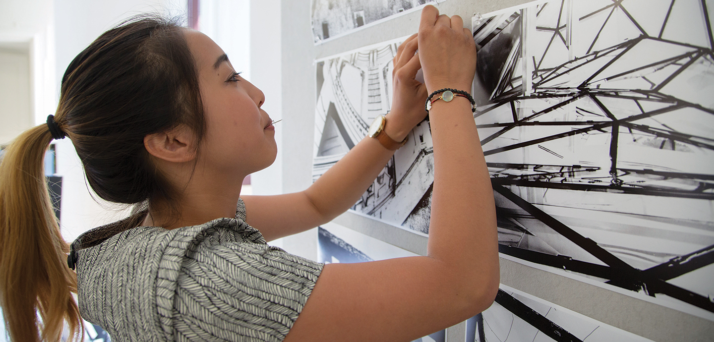 Student in photo class pins her work to a wall prior to review.