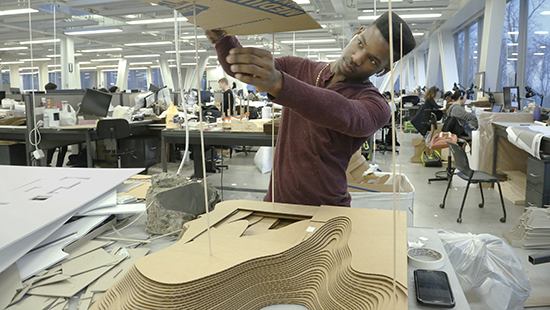 young man working with a stacked cardboard model in an architecture studio