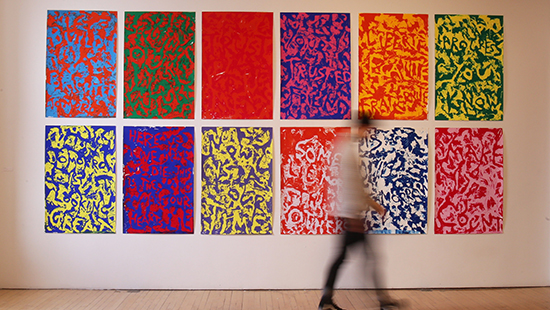 A series of 12 colorful posters mounted on a wall with a person moving in front of them
