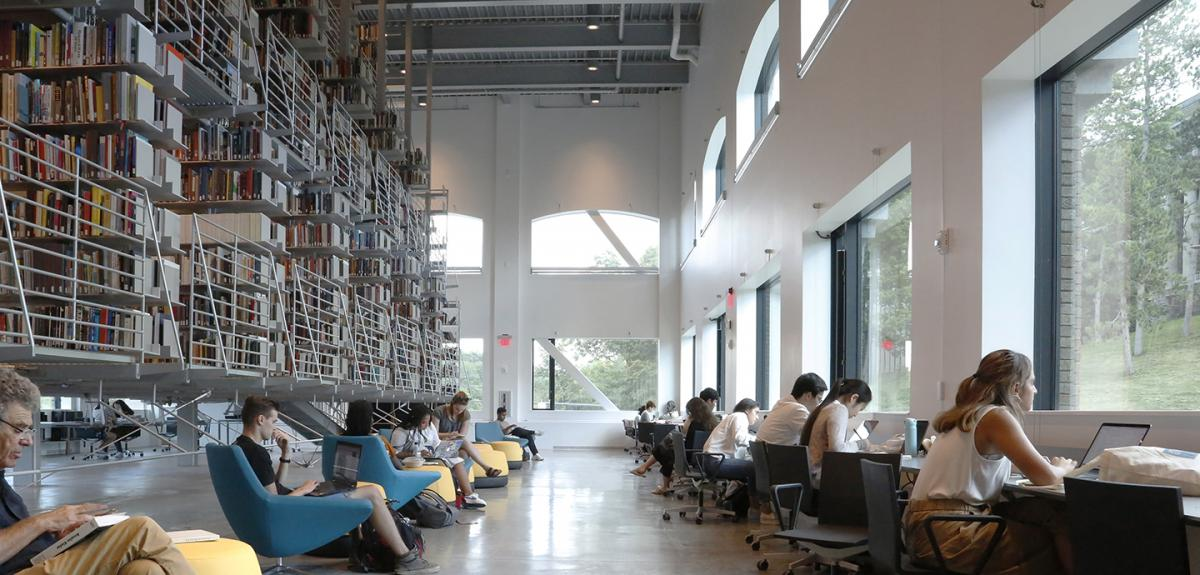 library of open stacks suspended from a ceiling with patrons on yellow and blue chairs along a bank of windows