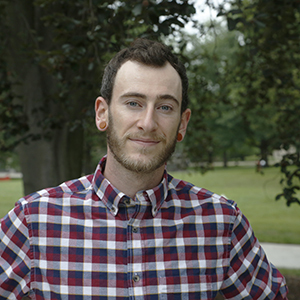 A person with facial hair and wearing a plaid shirt