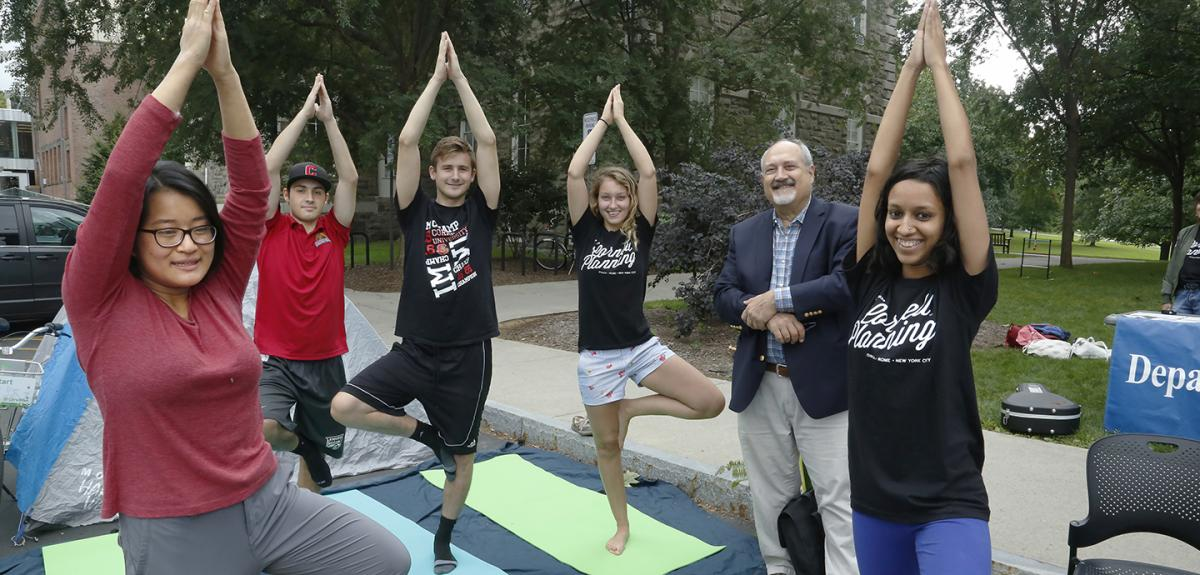 A group of students on yoga matts with their arms above their heads standing on one foot