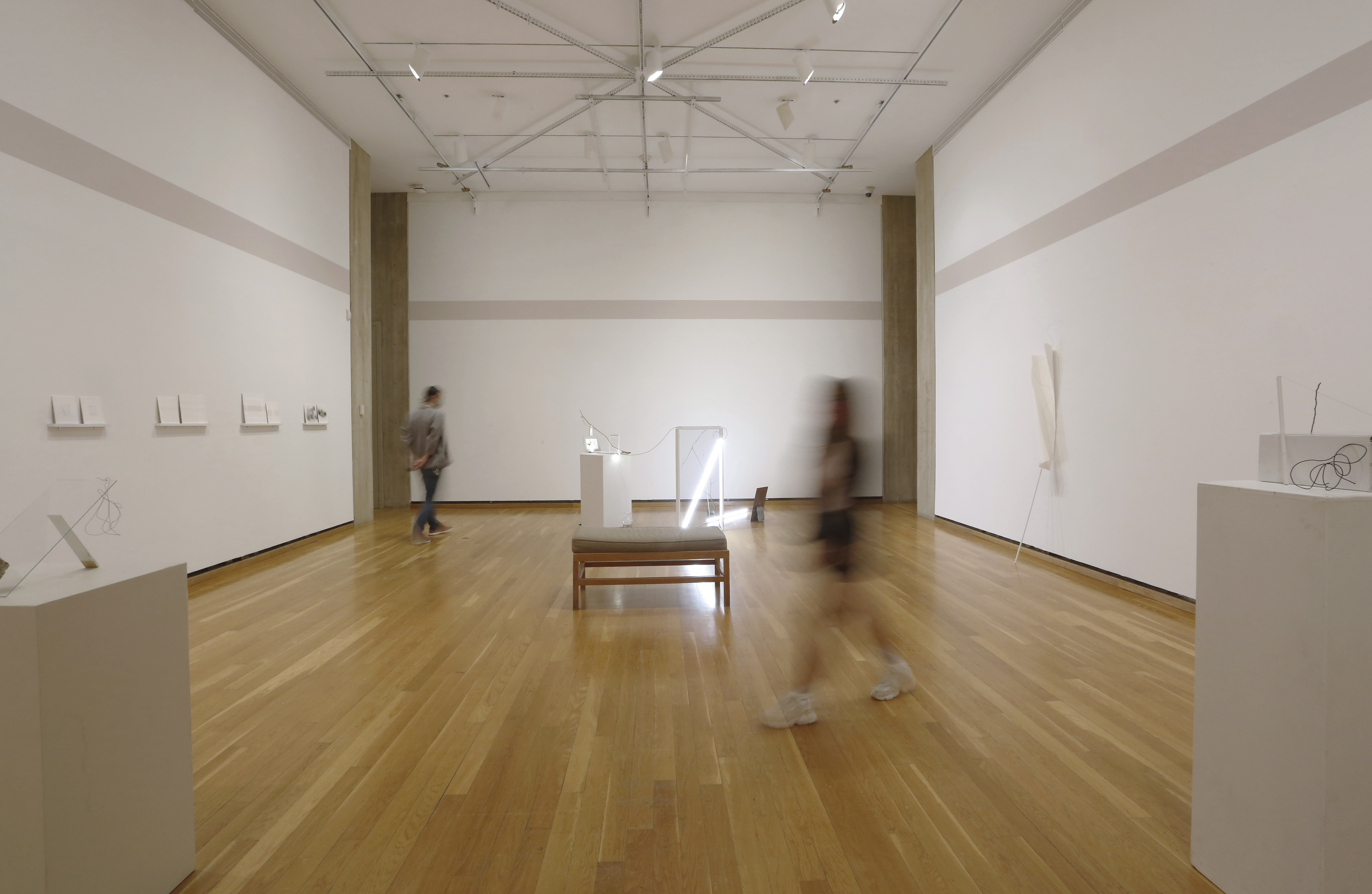 A person in a gallery with light wood flooring and white walls.