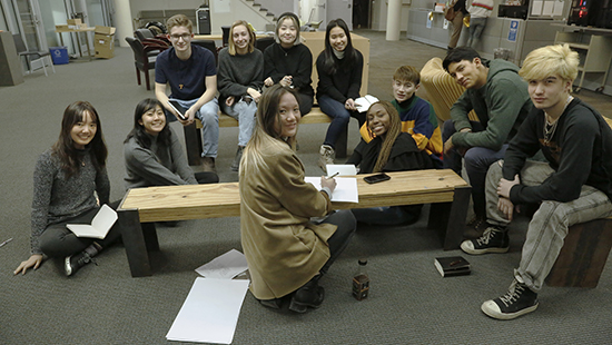 group of students seated on and around a wooden bench in a large room