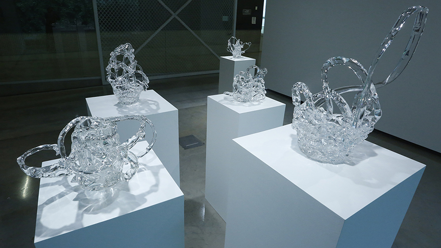 Glass sculptures on white pedestals.