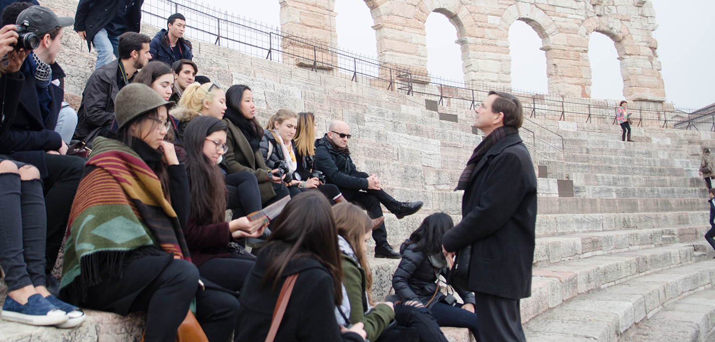 Jeffrey Blanchard describes to students an ancient colosseum during a trip to northern Italy.