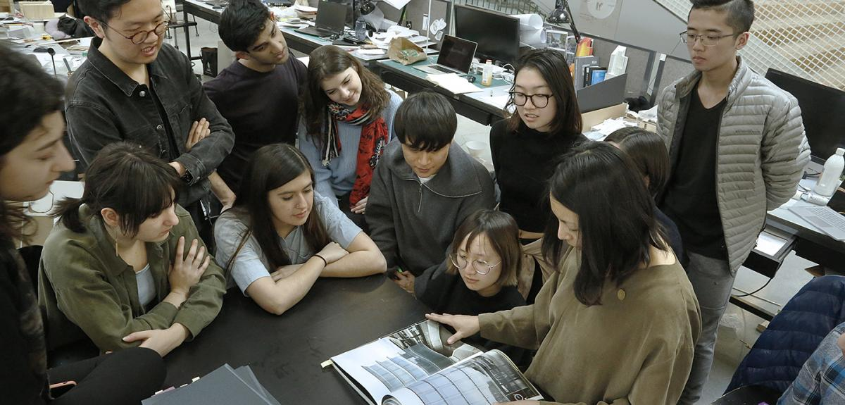 group of students and a faculty member gathered around a book they are discussing