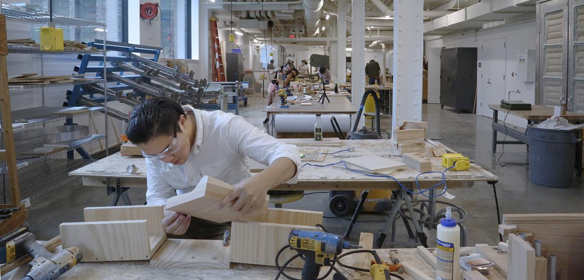 student working with wood and tools in a large open indoor space