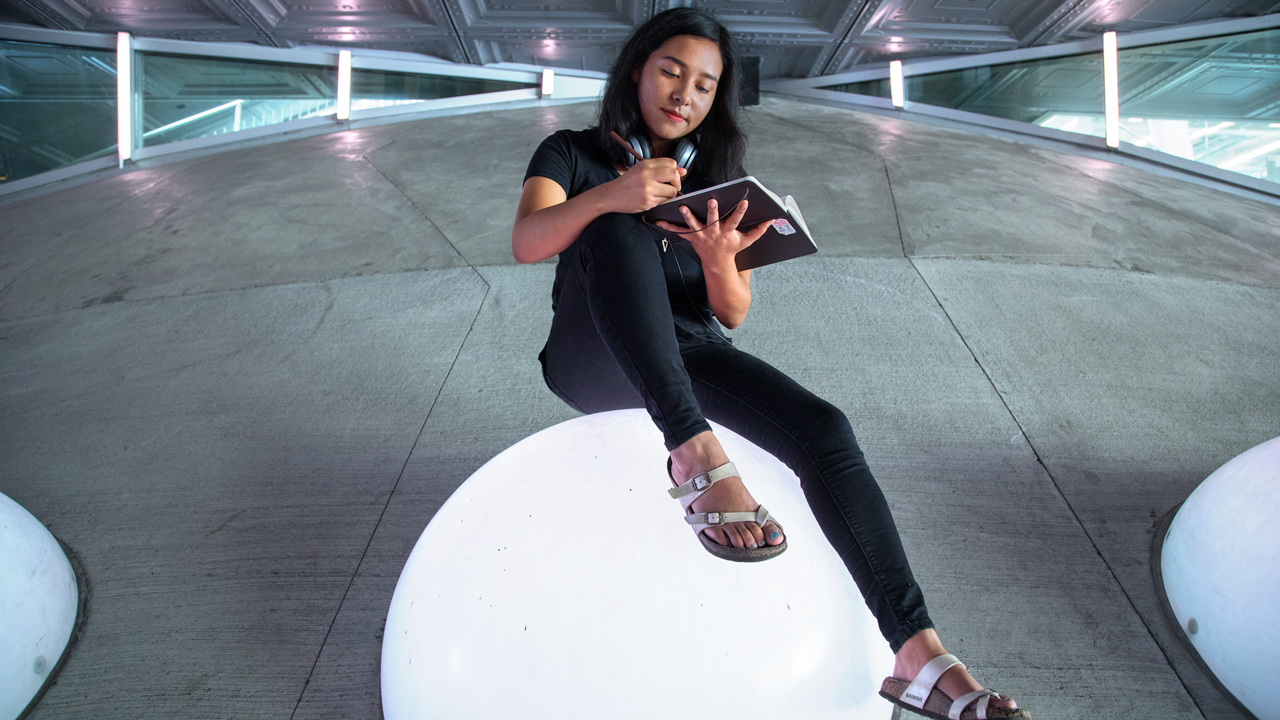 Student sitting and drawing on a white bubble structure