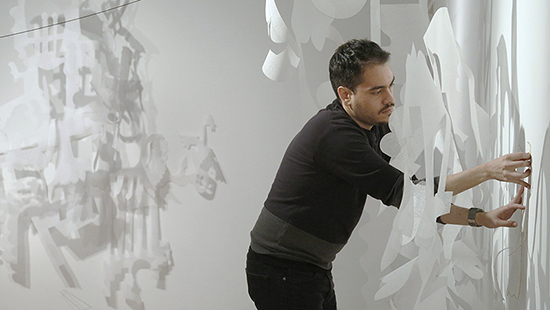 Student installing an exhibition of paper sculptures